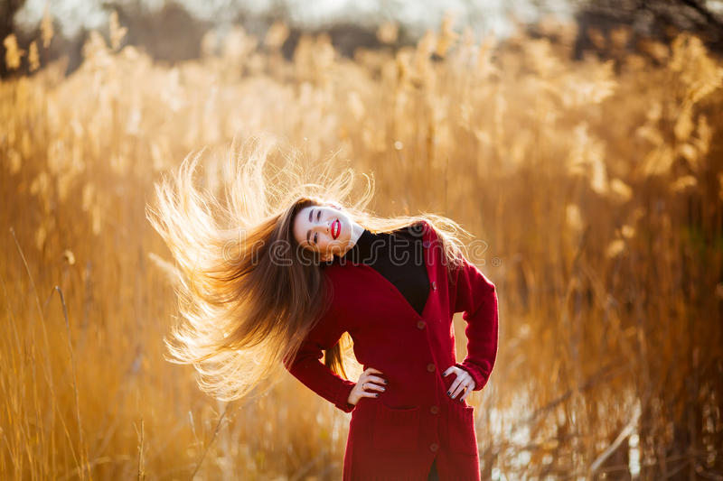Happy sniling young woman. Beautiful female with long healthy blowing hair enjoying sun light in park at sunset. Spring stock image