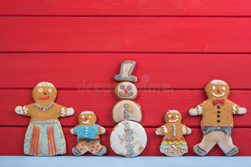Happy Snowman and gingerbread man family. Happy funny gingerbread man family on wooden background with Snowman stock photography