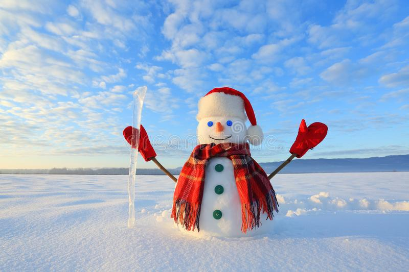 Happy snowman in hat, scarf, red gloves with ice pikestaff is standing on the snow lawn. Unbelievable sunrise. Mountains landscape stock photography