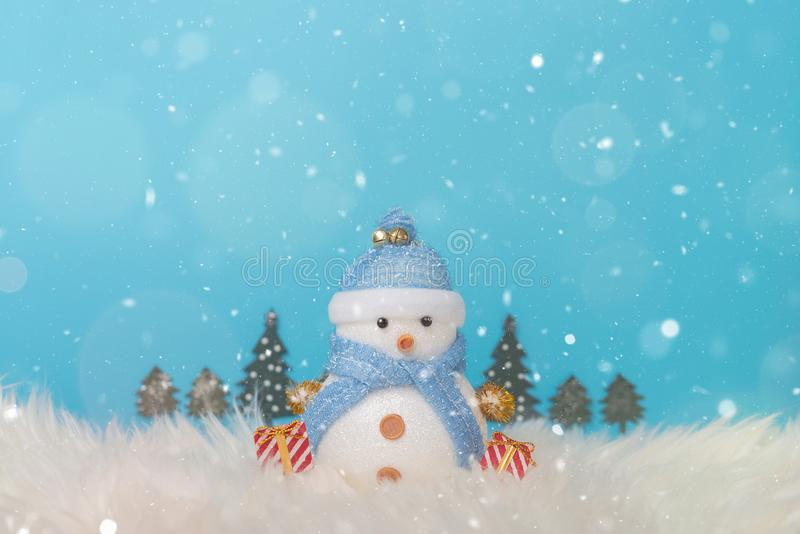 Happy snowman standing in blue winter christmas snow background. Christmas landscape with gifts and snow. Merry christmas and happ stock photography