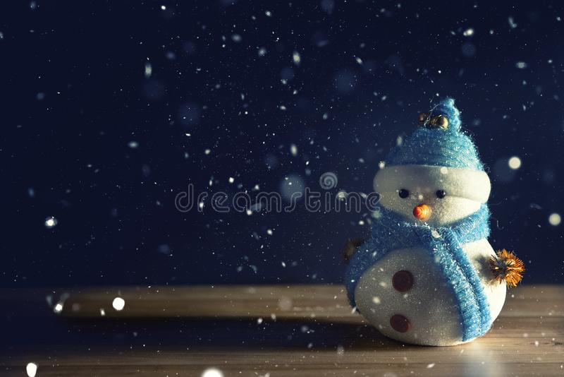 Happy snowman standing in dark winter christmas snow background. Merry christmas and happy new year greeting card with copy-space. stock photography