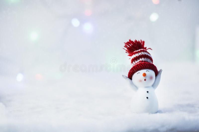 Happy snowman standing in winter christmas landscape. Merry christmas and happy new year greeting card. Funny snowman in hat on royalty free stock photos
