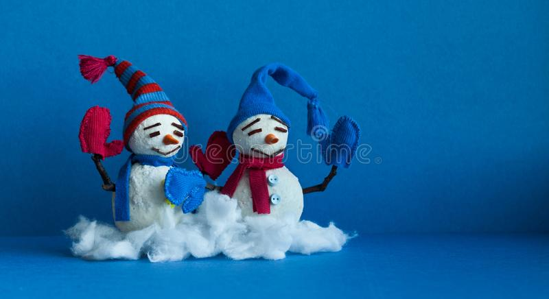 Happy snowmen on blue background. Winter traditional snowman characters with scarf mittens and funny hats. Xmas new year royalty free stock image