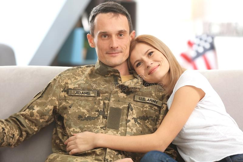 Happy soldier and his wife sitting on sofa. At home royalty free stock image