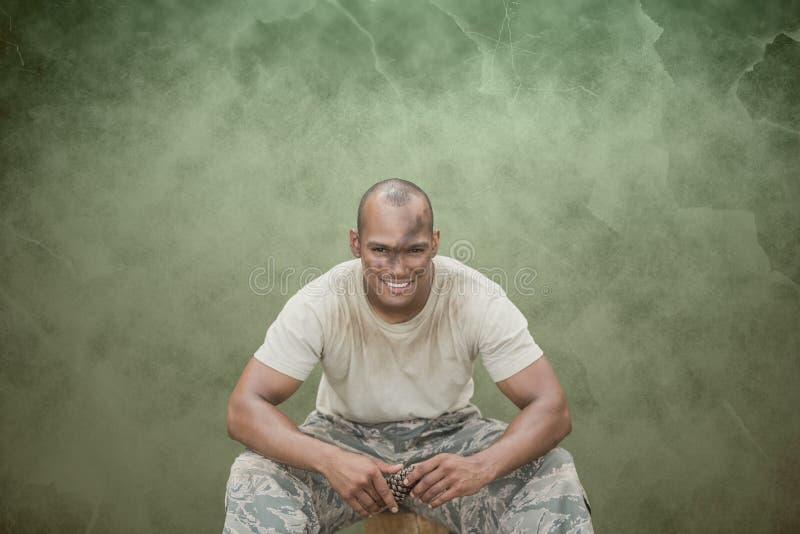 Happy soldier man sitting against green background. Digital composite of Happy soldier man sitting against green background royalty free stock photo