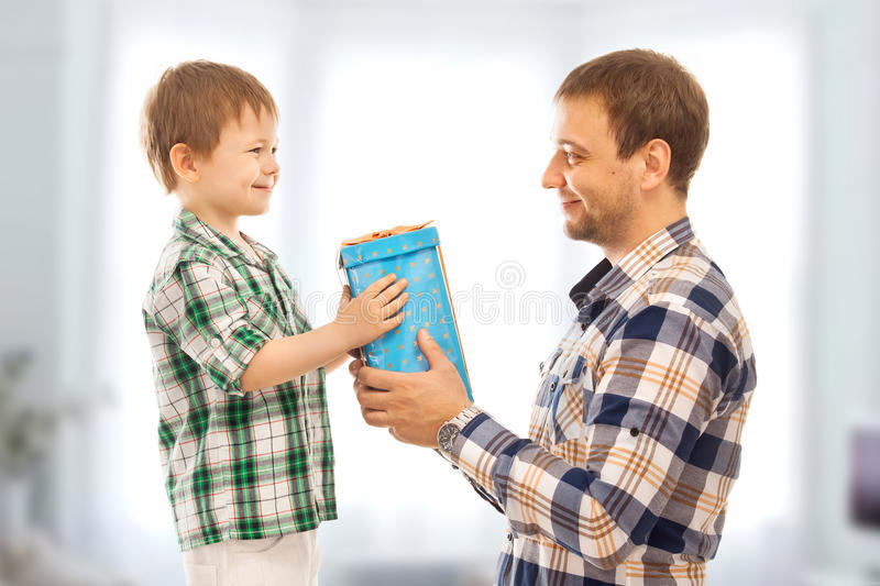 Happy son gives his father gift. Fathers day, family holiday, vacation stock photography