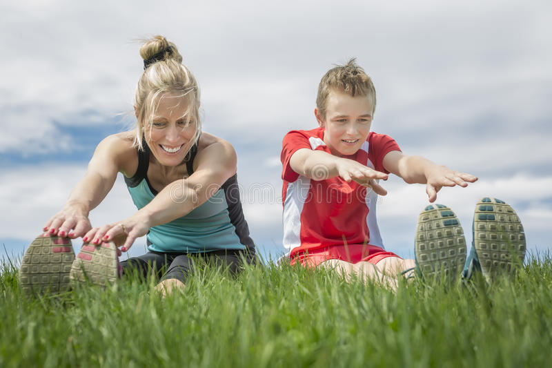 Happy son and mother are doing exercises in the summer park stock photos