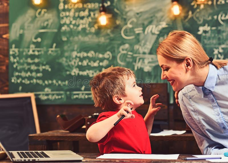 Happy son and mother have lesson in drawing. Boy and woman smile at school desk. Woman teach little child to paint. Happy son and mother have lesson in drawing royalty free stock image