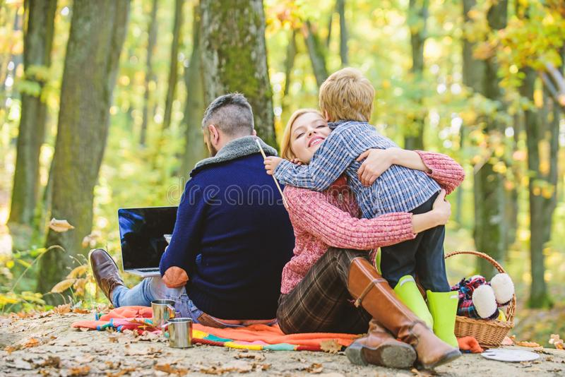 Happy son with parents relax in autumn forest. Mother, father love their little boy child. Fall weather. Wine or coffee stock photo