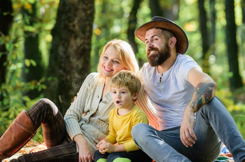 Happy son with parents relax in autumn forest. Sunny weather. Healthy food. Mother, cowboy father love their little boy. Child. Spring mood. Happy family day stock photography