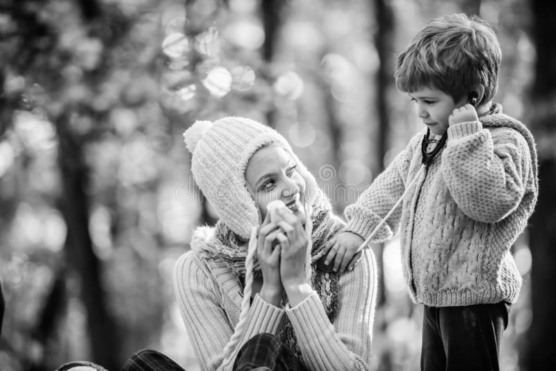 Happy son play with mother like doctor. relax in autumn forest. Spring mood. seasonal cold. Happy family day. Mother royalty free stock photo