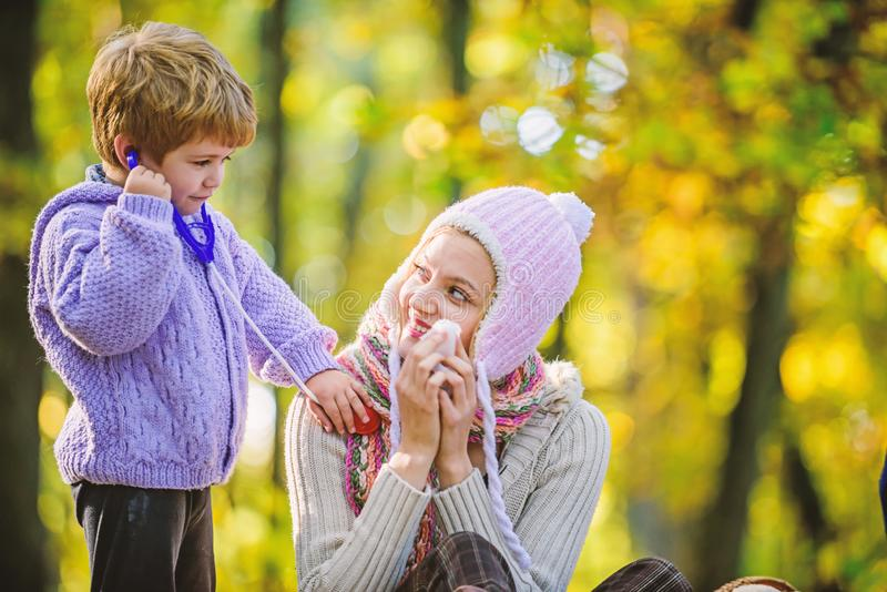 Happy son play with mother like doctor. relax in autumn forest. Spring mood. seasonal cold. Happy family day. Mother. Love her small boy child. cold weather stock image