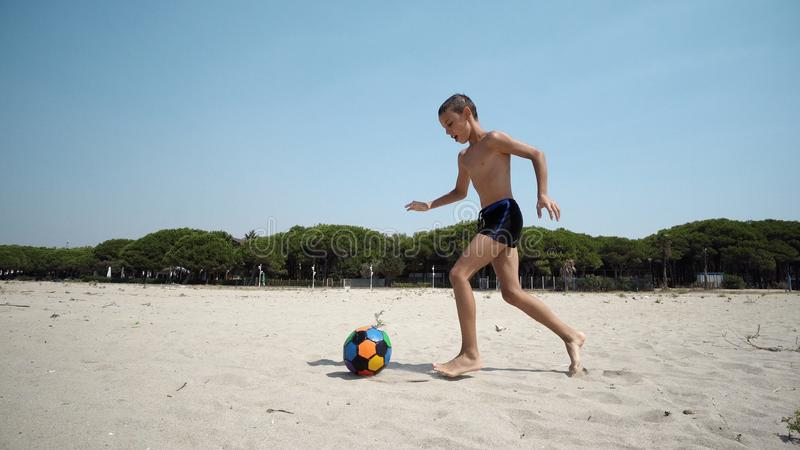 Happy son play soccer or football on the beach having great time on summer holidays stock photo