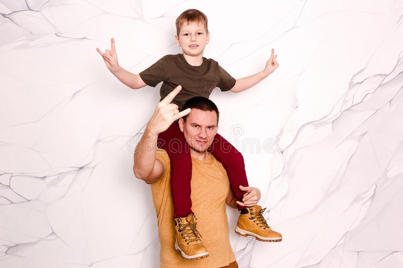 Son sits on his father`s neck stock photo