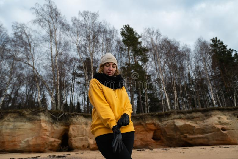 Happy sport and fashion lover enthusiast working out on a beach wearing bright yellow sweater and black gloves and a cap royalty free stock photos