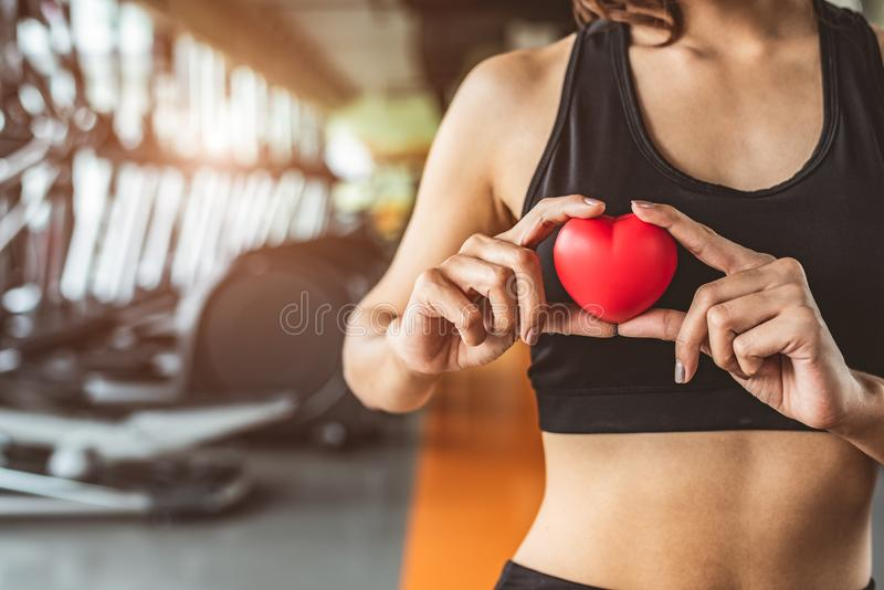 Happy sport woman holding red heart in fitness gym club. Medical cardio heart strength training lifestyle. Pretty female sport stock photo