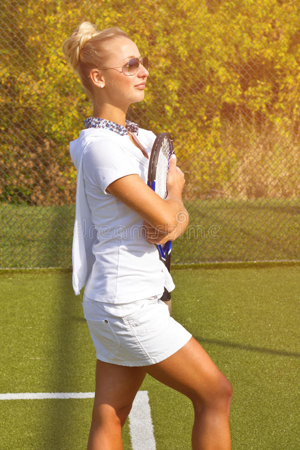 Happy sports girl stands with racket on court at sunny summer day stock photos