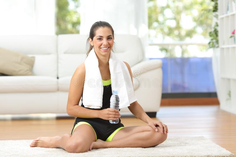 Happy sportswoman posing with bottled water at home royalty free stock images