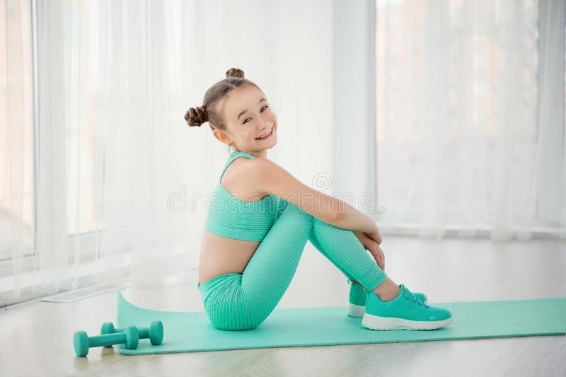 Little sporty girl gymnast in sportswear doing exercises on a mat indoor stock photography