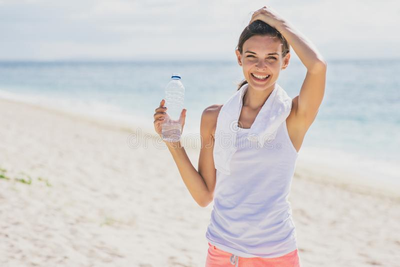 happy sporty girl holding a bottle of mineral water for refreshment stock images