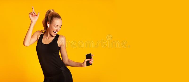 Happy Sporty Girl Holding Handy Tanz über gelbes Hintergrund lizenzfreie stockbilder