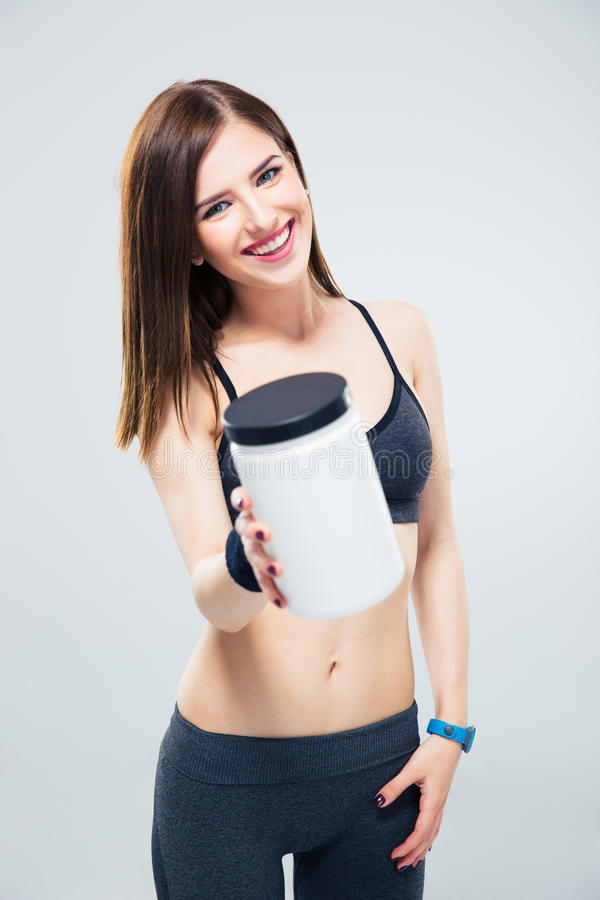 Happy sporty woman giving jar of protein on camera royalty free stock image