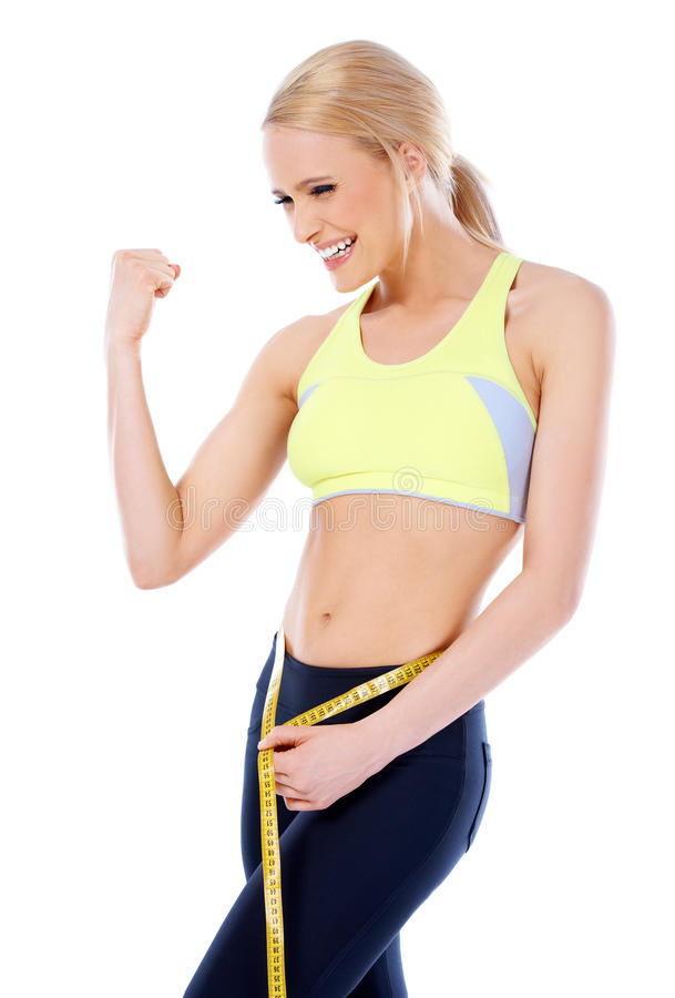 Happy sporty woman showing her muscle. While measuring her waist royalty free stock image