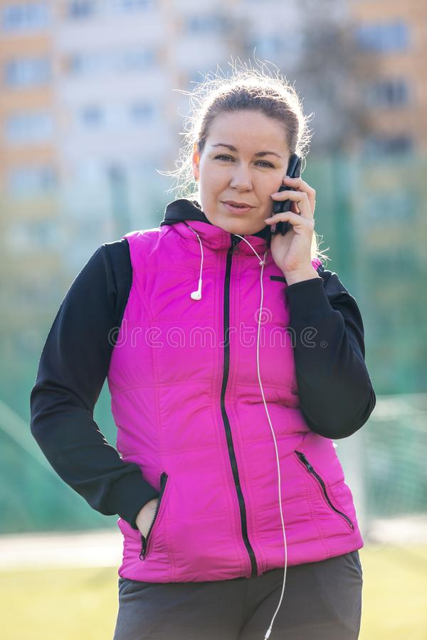 Happy sporty woman with smartphone. Female athlete using smartphone during workout rest royalty free stock photos