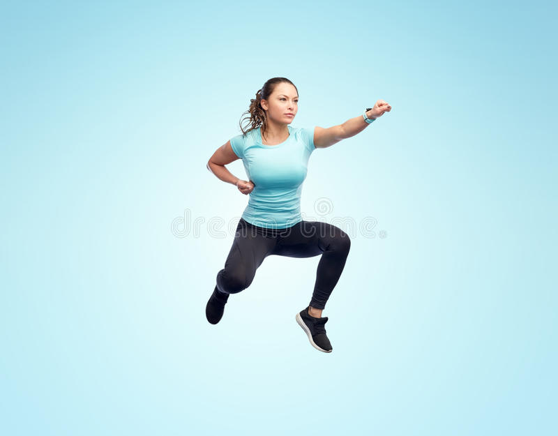 Happy sporty young woman jumping in fighting pose. Sport, fitness, motion and people concept - happy young woman jumping in air in fighting pose over blue stock photography