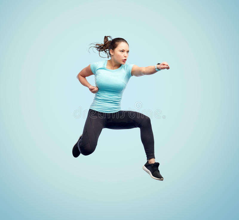 Happy sporty young woman jumping in fighting pose. Sport, fitness, motion and people concept - happy young woman jumping in air in fighting pose over blue royalty free stock photo