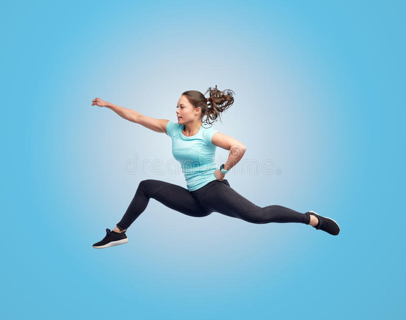 Happy sporty young woman jumping in fighting pose. Sport, fitness, motion and people concept - happy young woman jumping in air in fighting pose over blue royalty free stock image