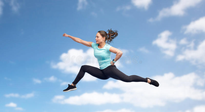 Happy sporty young woman jumping in fighting pose. Sport, fitness, motion and people concept - happy young woman jumping in air in fighting pose over blue sky stock photo