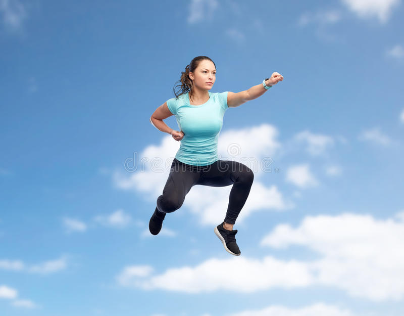 Happy sporty young woman jumping in fighting pose. Sport, fitness, motion and people concept - happy young woman jumping in air in fighting pose over blue sky stock photos