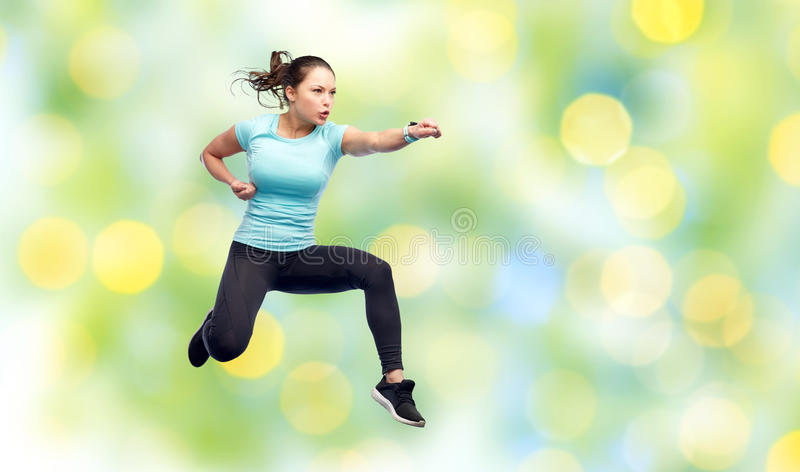 Happy sporty young woman jumping in fighting pose. Sport, fitness, motion and people concept - happy young woman jumping in air in fighting pose over summer stock photo
