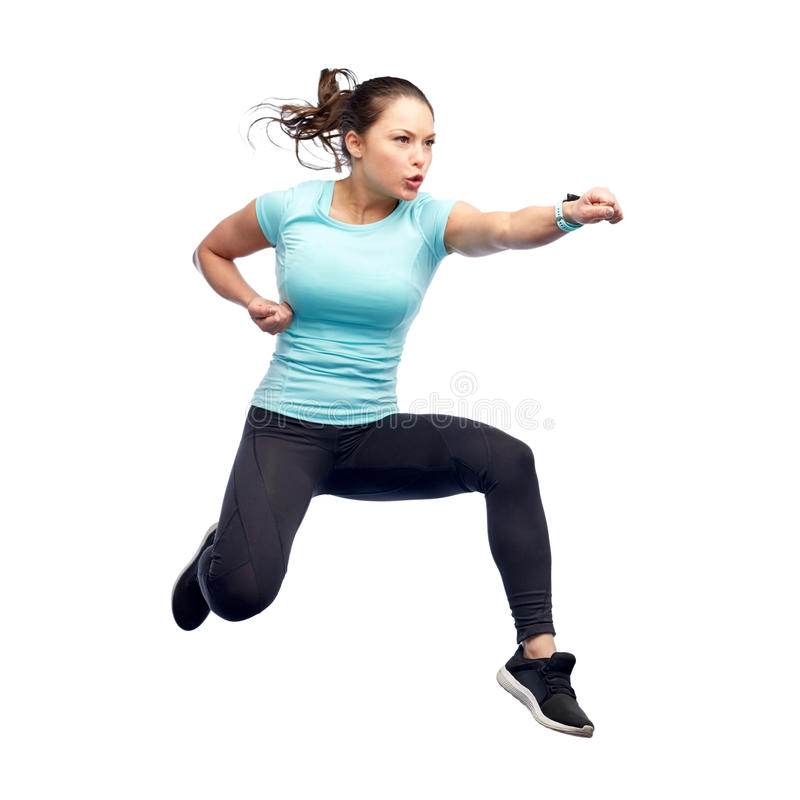 Happy sporty young woman jumping in fighting pose. Sport, fitness, motion and people concept - happy young woman jumping in air in fighting pose over white royalty free stock photo