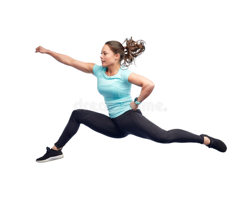 Happy sporty young woman jumping in fighting pose. Sport, fitness, motion and people concept - happy young woman jumping in air in fighting pose over white stock images
