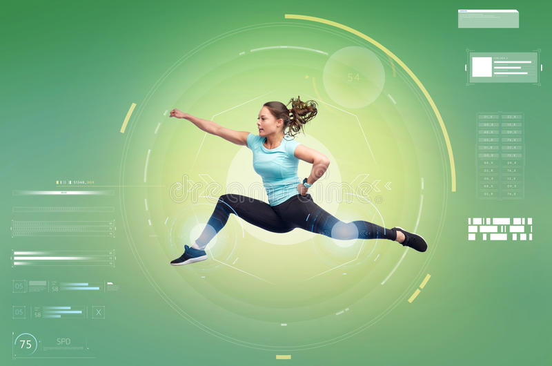 Happy sporty young woman jumping in fighting pose. Sport, fitness, technology, motion and people concept - happy young woman jumping in air in fighting pose over stock image