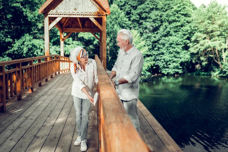 Happy spouses hanging a heart sign on the wooden bridge royalty free stock images