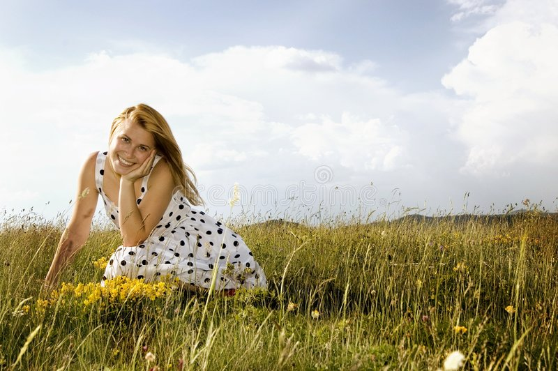 Happy spring. Woman lie on a green field with yellow flowers under blue sky