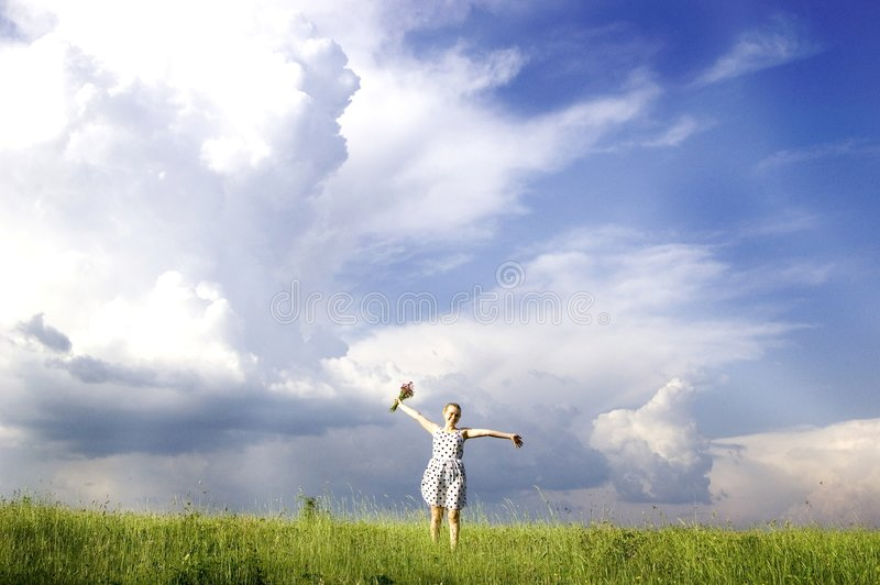 Happy spring. Happy woman in a field of flowers under blue sky