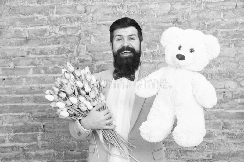 Happy spring day. man in love. Spring gift. Bearded man hipster with flowers. Bearded man with tulip bouquet, bear. Love stock photo