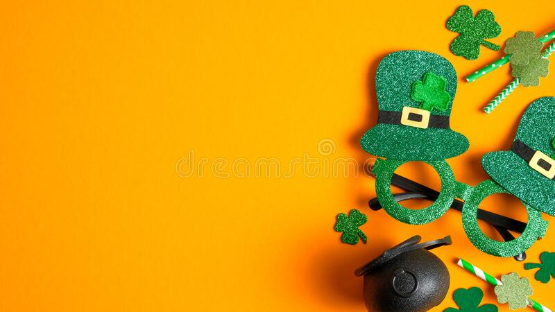 Happy St Patrick`s Day concept. Flat lay composition with St Patricks Day party glasses, drinking straws decorated shamrock leaf royalty free stock image