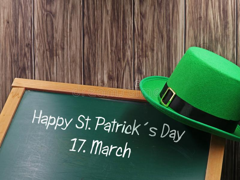 Happy St. Patricks Day chalk text with green hat on blackboard and wooden background for copy space stock images