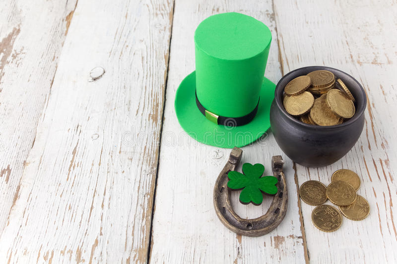 Happy St Patricks Day leprechaun hat with gold coins and lucky charms on vintage style white wood background. Top view stock images
