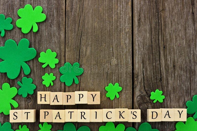 Happy St Patricks Day wooden blocks with shamrocks over wood royalty free stock image