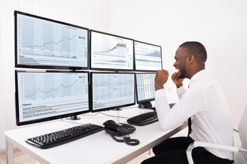 Happy Stock Market Broker Looking At Graphs On Multiple Computer. Happy Young Male Stock Market Broker Looking At Graphs On Multiple Computer In Office royalty free stock photos