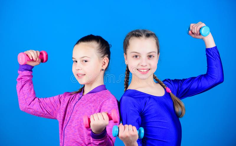 Happy strong children with barbell. workout of strong small girls hold dumbbell. weight lifting for muscules. Fitness. Diet for energy health. Sport success stock photo