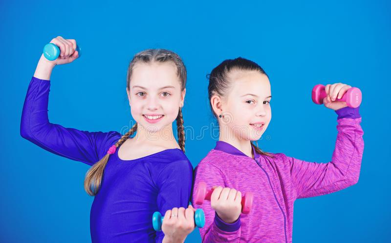Happy strong children with barbell. workout of strong small girls hold dumbbell. weight lifting for muscules. Fitness. Diet for energy health. Sport success stock photos
