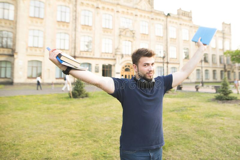 Happy student with books and a notebook in the hands of a university campus. Portrait of a happy man with a beard on the background of a university building stock image