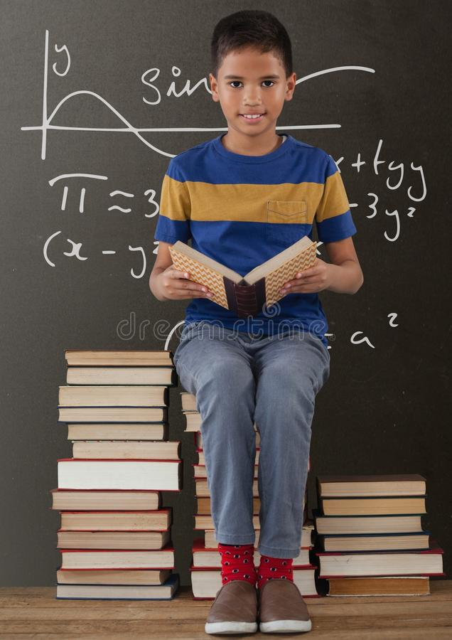 Happy student boy on a table reading against grey blackboard with education and school graphics royalty free stock photos